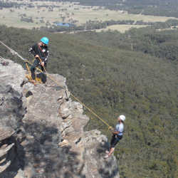 Abseiler is lowered offer the cliff in the Blue Mountains