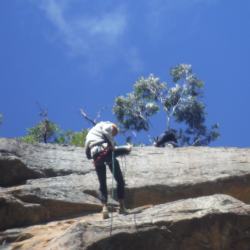 Looking up at an abseiler from the bottom of the cliff in the Watagans National Park