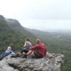Three hikers resting on a rock in the Watagans National Park