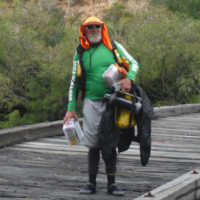 A man standing on a bridge fully covered for sun protection