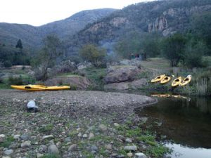 A beautiful campsite with Kayaks on the shore of the Snowy River Kayak Adventure