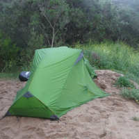 a tent is set up on the sand next to the river on the snowy river kayak adventure