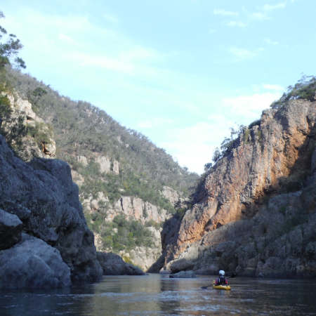 A paddler sits and surveys the river ahead between cliffs that rise up each side of him on the Snowy River kayak adventure