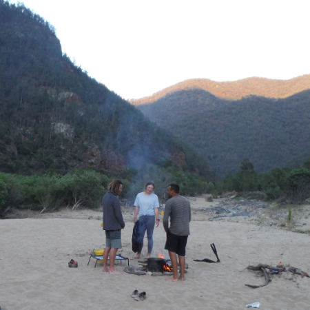 three people standing by a camp fire at redneck campsite, on day two of the snowy river kayak adventure