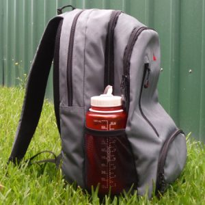 A small backpack sitting on the grass showing size of bag needed for bus tour to Barrington River Kayak tour
