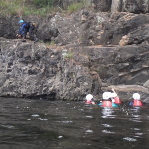 people are in the Barrington river climbing up a rock face to jump back into the water