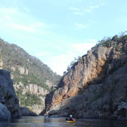 A lone kayaker is paddling through a rock gorge on the Snowy River