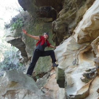 A person is climbing through a gap in the rocks on the Watagan National Park Discovery Tour