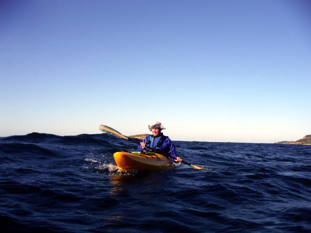 A person is Kayaking across to the island on the Kayak Port Stephens Broughton Island tour